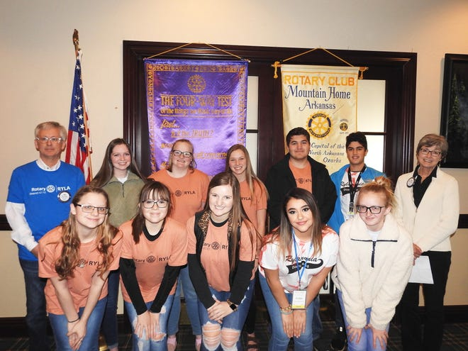 """On Dec. 12, the special guests of the Rotary Club of Mountain Home were some of the 13 area students that the club had sent to Rotary Youth Leadership Awards this past fall. These juniors from Cotter High and Mountain Home High spent a four-day weekend at camp in Oklahoma with hundreds more from the four-state Rotary district. They were accompanied by RYLA chair Rick Steiner and Rotary board member Renae Schocke, who were both camp chaperones. The young people learned self-discipline, formed bonds and friendships, built self-confidence, and trusted each other for support and encouragement. Mark Hopper with the Past Presidents Council also presented the """"Featured Rotarian of the Month"""" to Perry McDonald (November) and to RYLA Coordinator Rick Steiner (December). They join Trevor Himschoot, who was selected for October. Rotarians also volunteered to ring Salvation Army bells this week, promoting the Rotary slogan of """"Service Above Self."""" Pictured on the front row (left to right) are: Samara Nodine (MHHS), Courtney Benedict (CHS), Hailey Cordell (CHS), Amber Trevino Stevenson (MHHS), Danni Hurst (CHS). Back row (left to right): Rotarian RYLA coordinator Rick Steiner, Kally Benedict (CHS), Aimee Tardiff (CHS), Kinsey Raley (MHHS), Tanner Connelley (MHHS), Armin Mortazi (MHHS), and Rotarian chaperone Renae Schocke."""