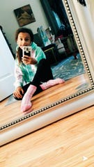 11-year-old Amaya Baker takes a selfie as she wears her oversized sweatshirt and black leggings.