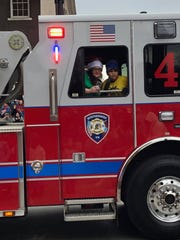 Jacqueline Hirlston and her son, Jaiden Dickson, ride in a Murfreesboro Fire and Rescue Department truck during the Christmas parade Dec. 8. Jaiden gained notoriety after a video of him making a basketball goal with help from the opposing team.