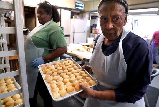 Louise Smith, removes the cooled yeast biscuits from a rack at the G & W Hamery, in Murfreesboro, on Thursday Dec. 19, 2019.