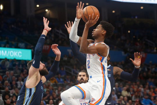 Oklahoma City Thunder guard Shai Gilgeous-Alexander (2) goes up for a shot between Memphis Grizzlies center Jonas Valanciunas, left, and forward Jae Crowder, right, in the first half Wednesday, Dec. 18, 2019, in Oklahoma City.