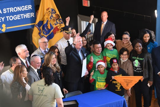 After signing legislation allowing undocumented immigrants to obtain a state driver's license, Gov. Phil Murphy and other public officials react together at the Snyder Academy in Elizabeth on 12/18/19.