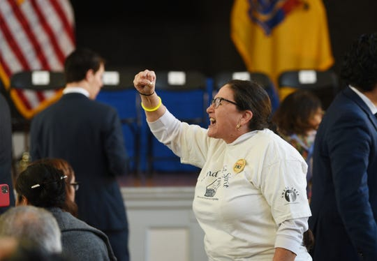 Diana Mejia, a member of Wind of the Spirit, cheers the crowd prior to Gov. Phil Murphy signs legislation allowing undocumented immigrants to obtain a state drivers license, photographed at the Snyder Academy in Elizabeth on 12/18/19.