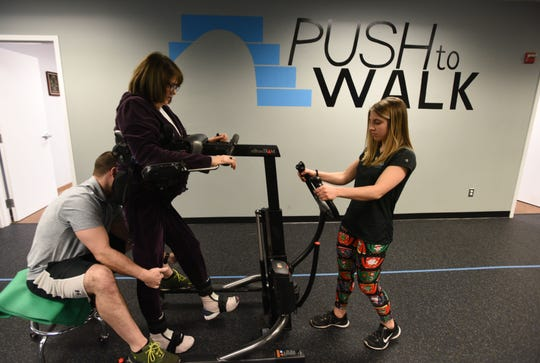 Trainers Chris Meola and Brittany Smith help Susan Dorfman, a Push to Walk client.