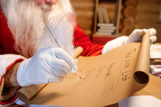 Santa looking over a list of who's naughty or nice.