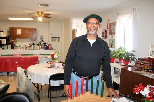 Rev. Warren Robinson of Owen Chapel AME Church of Alamogordo stands with a Kwanzaa menorah.