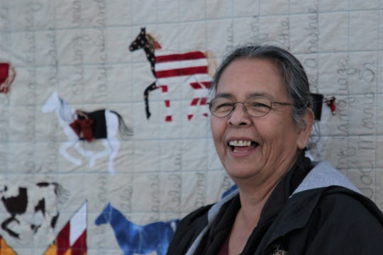 """Susan Henderson stands next to """"29 Warriors,"""" her quilt that will be featured in an upcoming episode of the PBS series Craft in America, outside of her studio in Ignacio, Colorado on Dec. 18, 2019."""