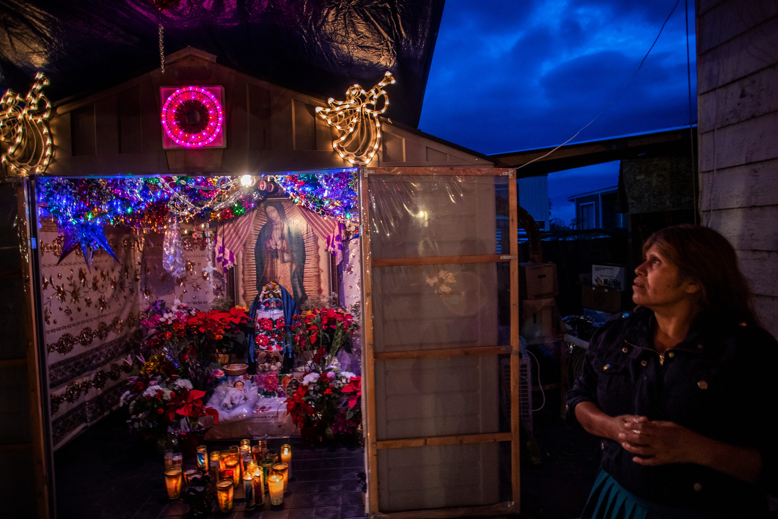 Maria Elias takes a moment to say a prayer to the Virgin of Guadalupe. The altar has been at her home for a year after she and her husband were selected as godparents by her Purépecha community, an honor bestowed every year on one of the families of the Purepecha in the Coachella Valley.