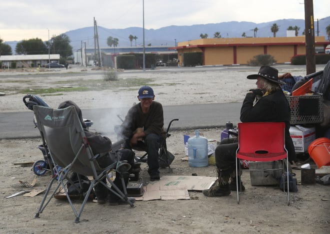 A group of men cook food in an empty lot in Indio, December 18, 2019.