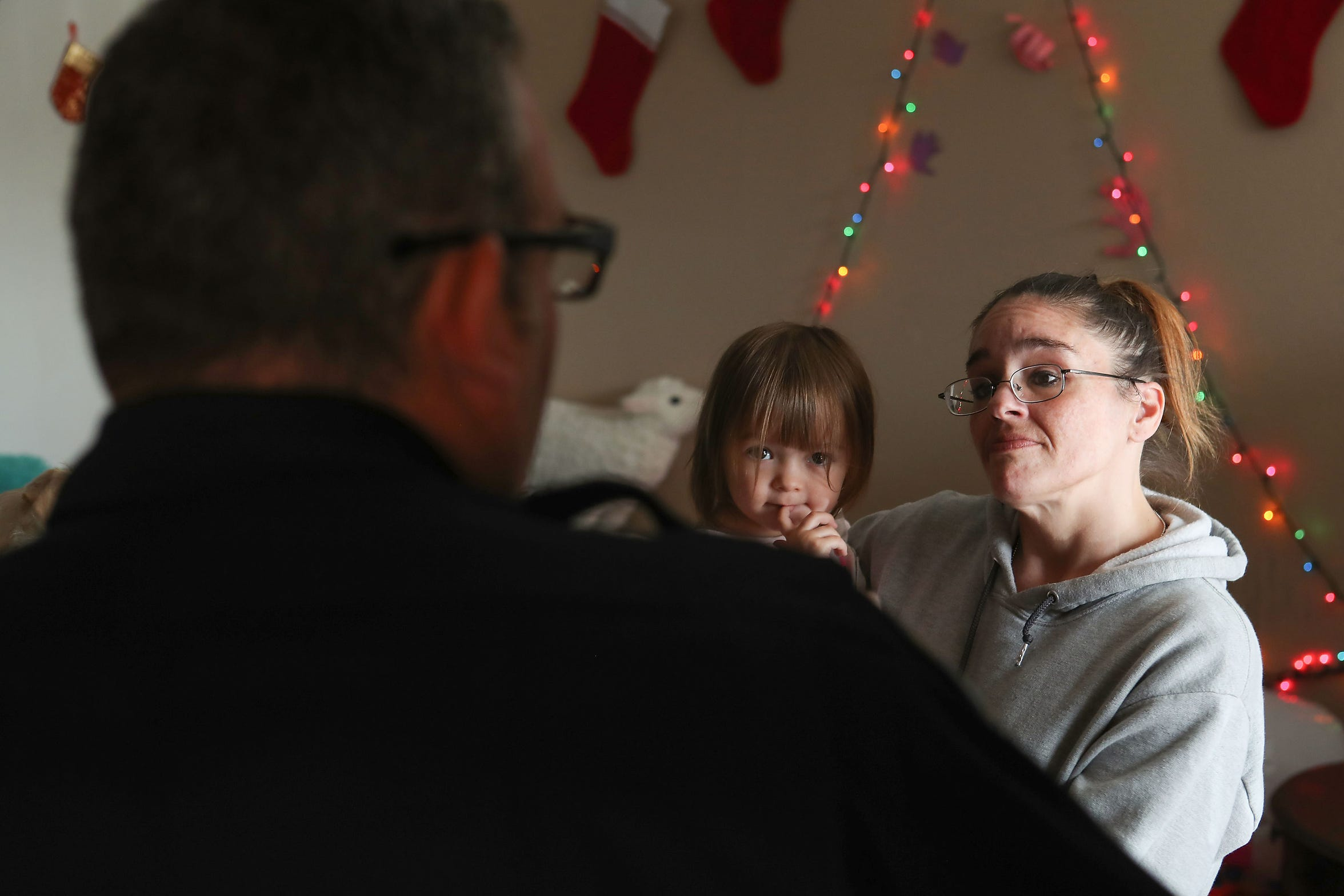 Erica Murphy holds her daughter Johanna in their apartment while being visited by Indio Police Officer Brandon Haworth.  Murphy spent seven years living homeless before getting back on her feet with some help from Haworth, December 18, 2019.