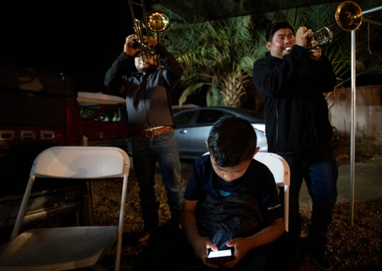 Band members, all of whom are Purepecha, perform during a rehearsal as a young boy entertains himself with a phone.