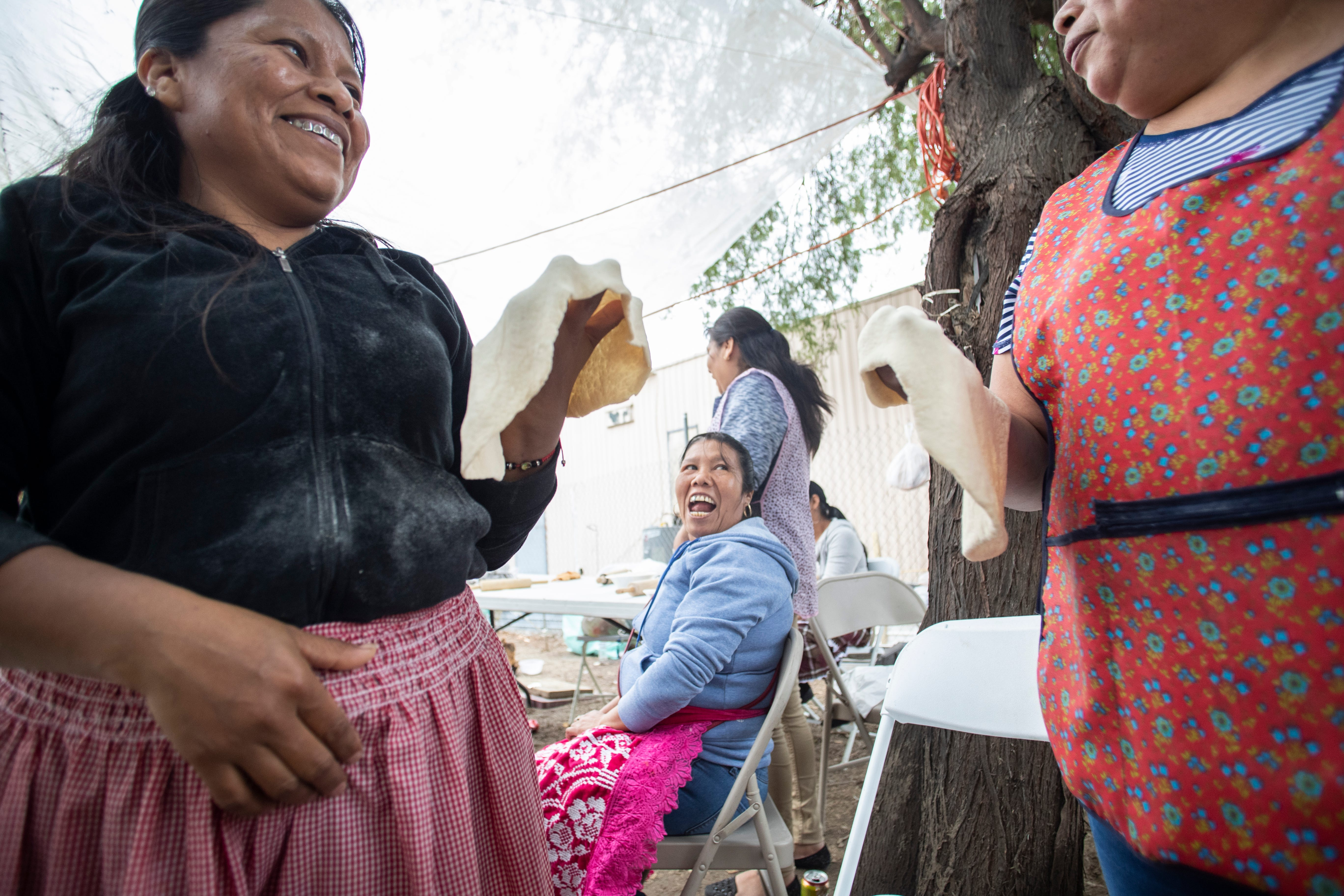 """From left Josefina Basilio, Macaria Pascual and Francisca Vicente enjoy a laugh while preparing """"buñuelos"""", a Mexican pastry made of flour."""