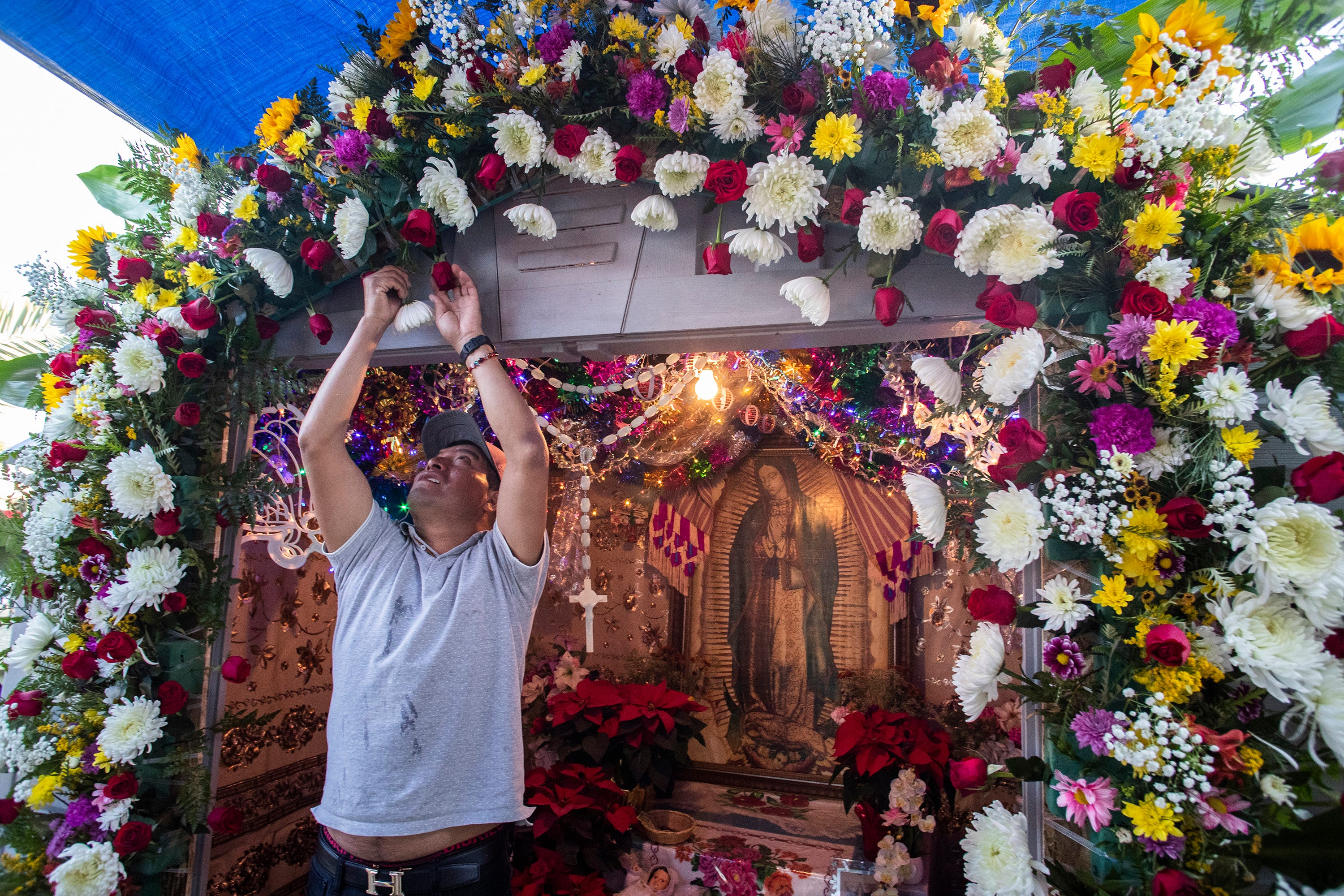 Martin Esteban arranges flowers on the altar to the Virgin of Guadalupe at the home of Audelio Diaz and Maria Elias. The Purepechas are recognized as some of the finest artisans in Mexico.