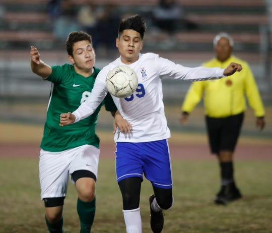 At left, Daniel Padilla of Coachella Valley High School battles for control of the ball against Indio High School's #39 during their game in Thermal on December 18, 2019.