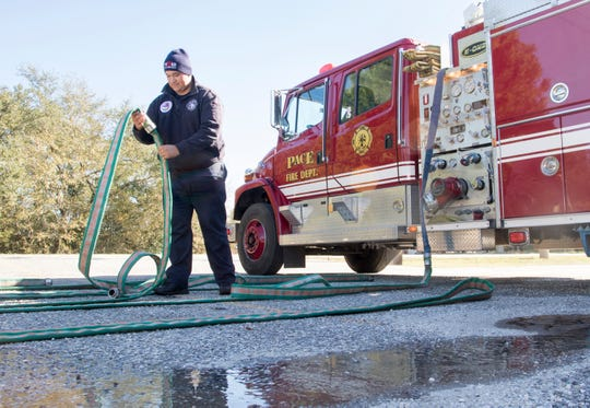 Firefighter William Gonzalez Barnes prepares to reload lines onto the fire truck after running a training exercise at the Pace Fire Rescue District's Wallace station #4 in Pace on Wednesday, Dec. 18, 2019.