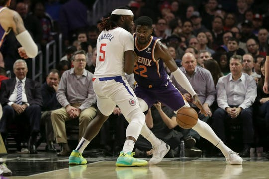 Phoenix Suns center Deandre Ayton drives around Los Angeles Clippers forward Montrezl Harrell during the first half of an NBA basketball game in Los Angeles, Tuesday, Dec. 17, 2019. (AP Photo/Chris Carlson)