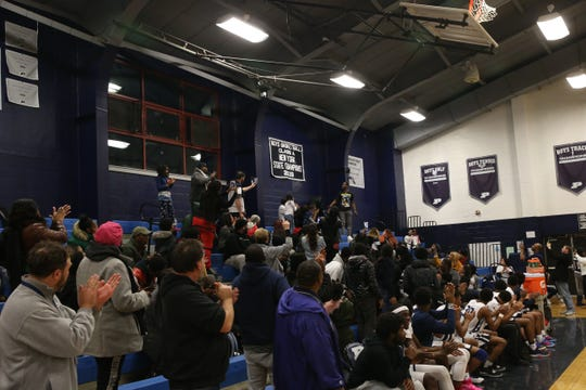 Members of the 2019 Poughkeepsie boys basketball team reveal a banner in the school gym from winning the state championships in the City of Poughkeepsie on December 18, 2019.