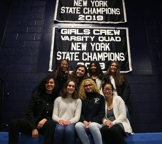 Members of the Poughkeepsie girls crew team below the banners hanging in the school gym from winning the 2019 state championships in the City of Poughkeepsie on December 18, 2019.
