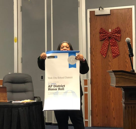 York City Superintendent Andrea Berry holds up a banner Wednesday, Dec. 18, recognizing the district's high school for making College Board's AP Honor Roll for the first time --  an distinction only given to two York County schools this year.
