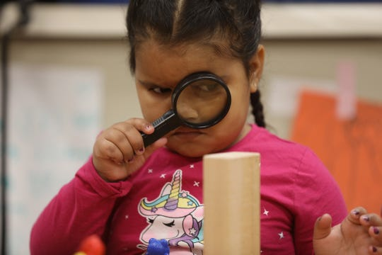 Annielie Perez uses a magnifying glass to study her wooden block in her pre-K class at Ibero Early Childhood Services on Clifford Avenue.