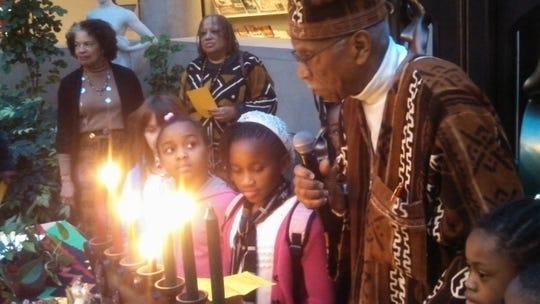 Dr. David Anderson, right, leads children through a Kwanzaa presentation at the Memorial Art Gallery.