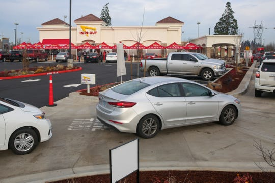 Cars queue in the drive-thru line of In-N-Out one week after its opening at Keizer Station, on Dec. 18, 2019.