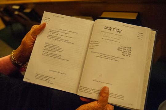 Leah Winter, holds a copy of the Torah during a Shabbat family service on Dec.13.
