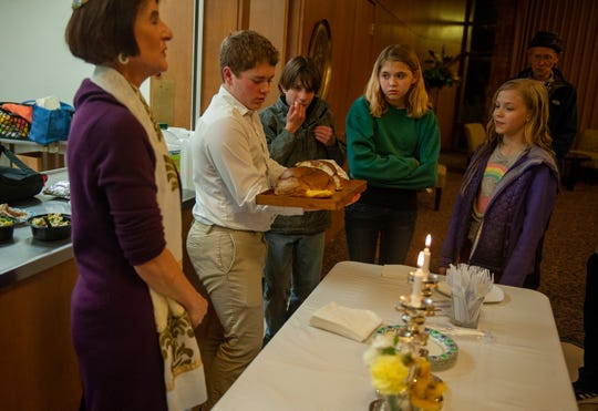 Noah Telford leads the prayers as he holds the Challah during a family service held once a month. Challah is a special bread in Jewish cuisine that's typically eaten on ceremonial occasions.