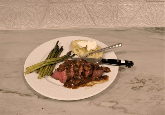Venison tenderloin with mushrooms and gravy are paired with asparagus and a baked potato in this photo from Greg Simons of San Angelo, who took what could be a record-breaking mule deer buck in Culberson County last month.