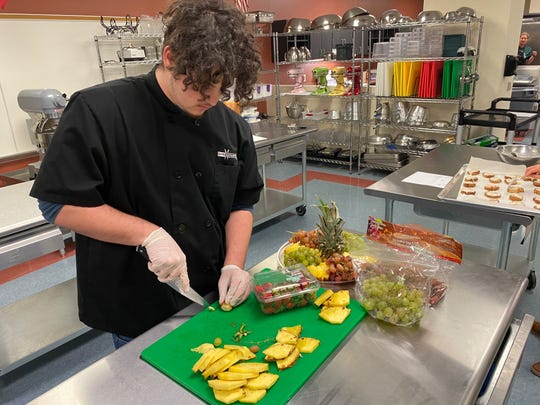 After slicing up a pineapple, San Angelo Lake View High School senior and Culinary Arts student Brandon McLester cuts strawberries to prepare a fruit plate. Dec. 19, 2019.