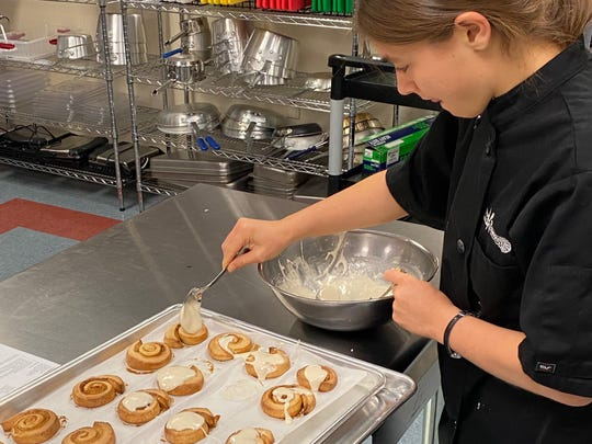 Lake View High School junior and Culinary Arts student Daisy Herr lays a dollop of glazed icing on a batch of cinnamon rolls Dec. 19, 2019.