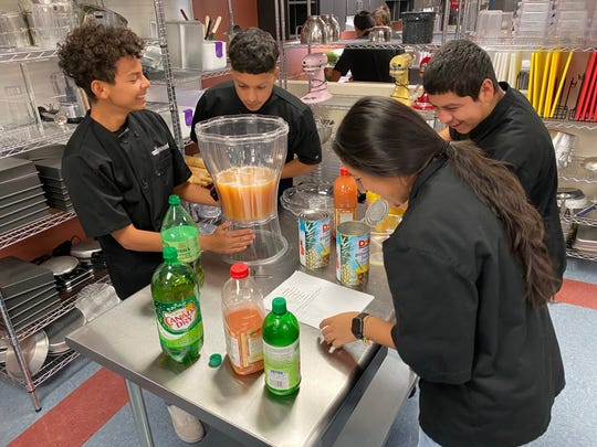 Lake View High School Culinary Arts students gather around a table mixing sodas and fruit juices to create a Christmas punch as part of class project Dec. 19, 2019.