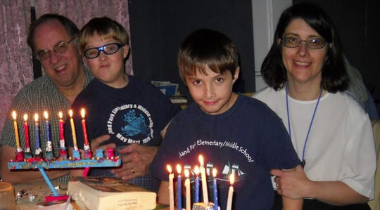 A family lights the menorah to celebrate Hanukkah.