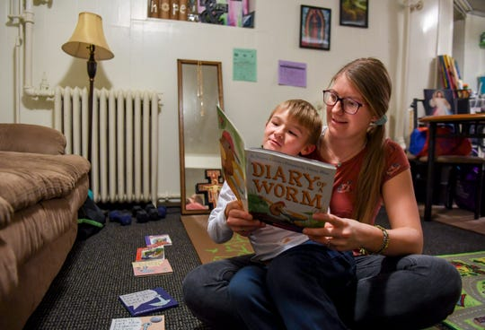 Emma Murtha sits with her son, Liam, 6, as he reads a book he brought home from school on Wednesday, Dec. 18, 2019 at their home in Sioux Falls.