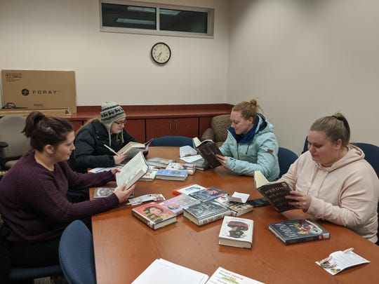 Brittany Fischer, Dawn Wille, Danielle Truax, and Teresa Schafer read books during the Young-At-Heart book club at the Brandon Library on Tuesday, Dec. 17.