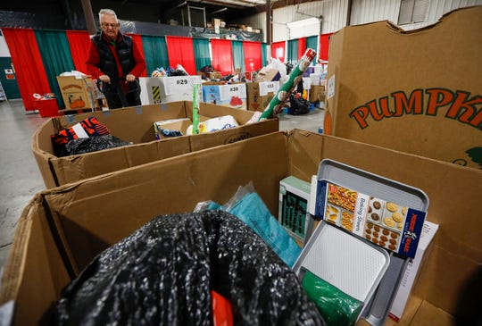 Brad Hoppes pulls out a box of toys and household items to take to a recipients vehicle during distribution day for Share Your Christmas at Crosslines on Thursday, Dec. 19, 2019.