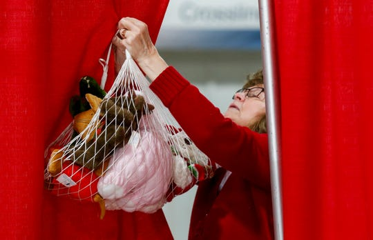 Volunteer Kathy Hoppes takes down a bundle of stuffed animals for a Share Your Christmas recipient at Crosslines on Thursday, Dec. 19, 2019.