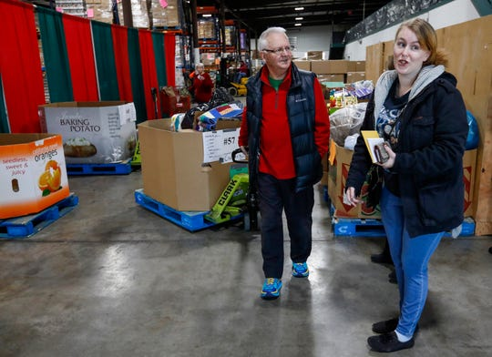Brad Hoppes talks with Denise Wright during distribution day for Share Your Christmas at Crosslines on Thursday, Dec. 19, 2019.