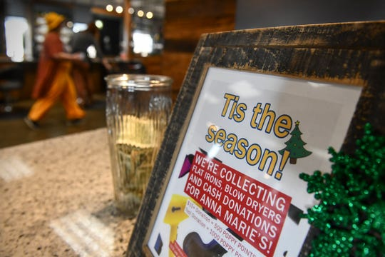 A sign highlights efforts to collect money and supplies for Anna Marie's Alliance Thursday, Dec. 19, 2019, at Poppy Salon in Waite Park,