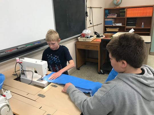 Paynesville Middle School students Derek Mergen, left, and Charles Stang sew together hospital sterilization sheets. The mats will be distributed to St. Cloud-area organizations for use by people experiencing homelessness.