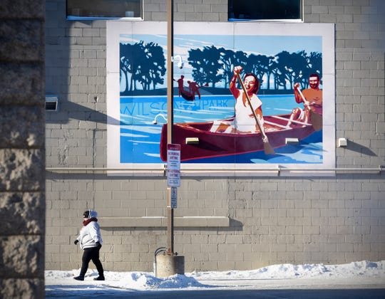A woman walks past a mural near the Metro Bus Transit Center Wednesday, Jan. 30, 2019, in downtown St. Cloud. Temperatures in the area were in the minus 30 range that morning.