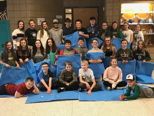 Paynesville Middle School students pose with homeless mats they helped sew together using hospital sterilization sheets.