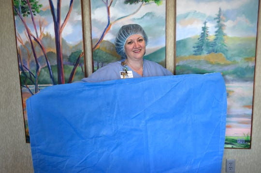 St. Cloud Hospital Perioperative Educator Supervisor Jodi Specht-Holbrook holds a mat made from two repurposed sterilization sheets.