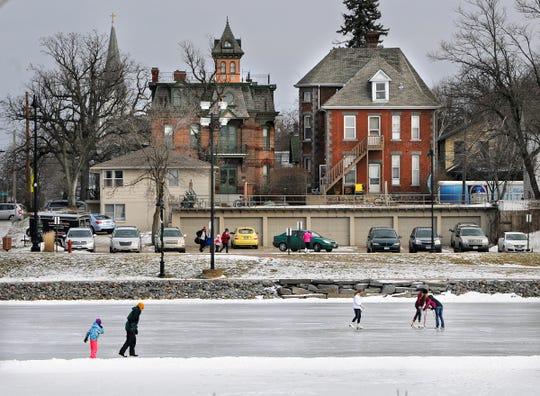 People enjoy warmer temperatures while skating on Lake George in St. Cloud.
