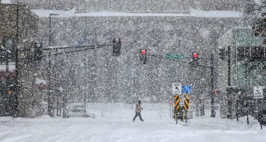 A pedestrian crosses the street near the Stearns County Courthouse as heavy snow falls.