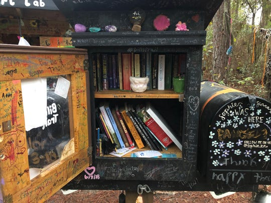 Little Free Library box containing an assortment of books, encouraging notes and signatures.