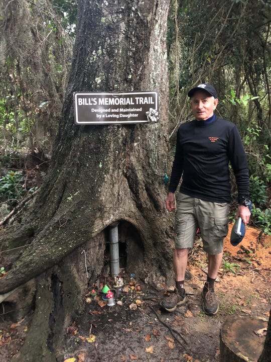 John Kalin stands by memorial sign at the head of Bill's Trail off the Lake Heritage Trail.