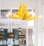 A Drybar hair dryer chandelier hangs in a Drybar blowout salon. Drybar hair dryers and other hair appliances are known for their neon yellow color.