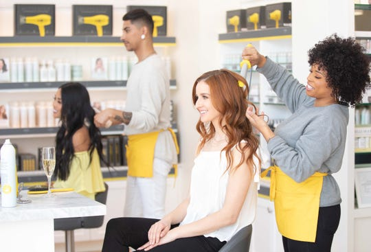 Stylists work at a Drybar salon, where Drybar hair-care products are used and sold, including its neon yellow hair appliances. El Paso's Helen of Troy has agreed to buy Drybar's products line while the California company will continue operate its 140 blowout salons.