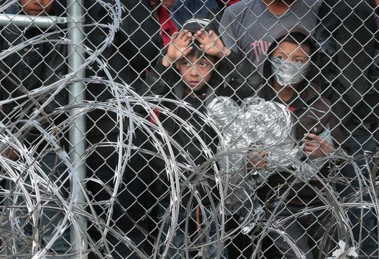 Asylum-seekers are kept in a fenced pen under the Paso Del Norte Bridge as they're processed. Hundreds of asylum-seekers from Central America were being held in the fenced-in area.